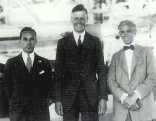 Edsel Ford, Charles Lindbergh, and Henry Ford pose in the Ford hangar during Lindbergh's August 1927 visit.