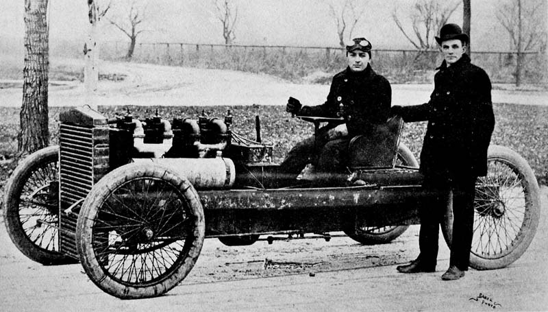 Ford (standing) launched Barney Oldfield's career in 1902. The 999 racer pictured.